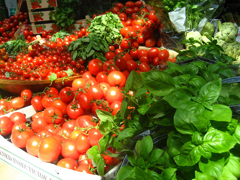market stall with copious tomatoes and basil leaves