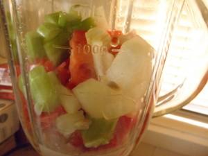 blender jug with onions, tomatoes, celery, almond milk, capsicum