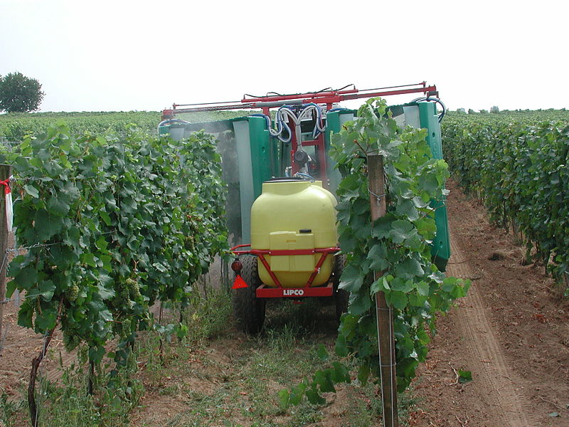 tractor spraying vines with pesticides