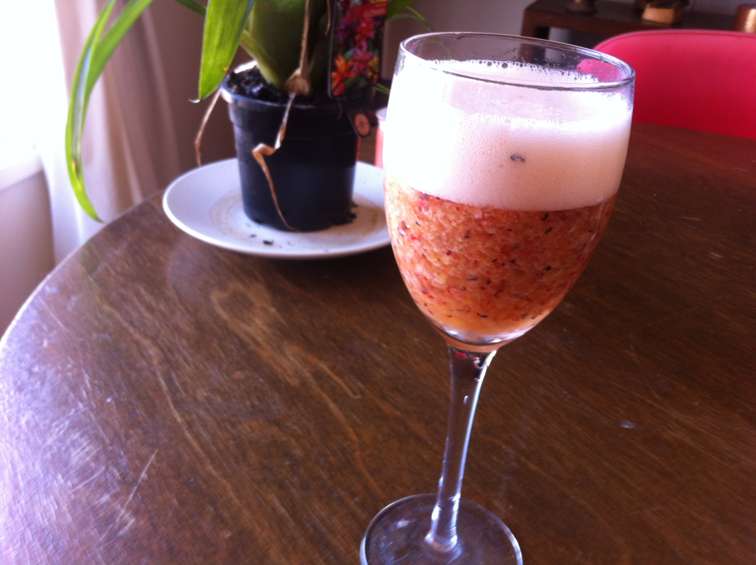 wine glass with cocktail in can see fruit with plant in background