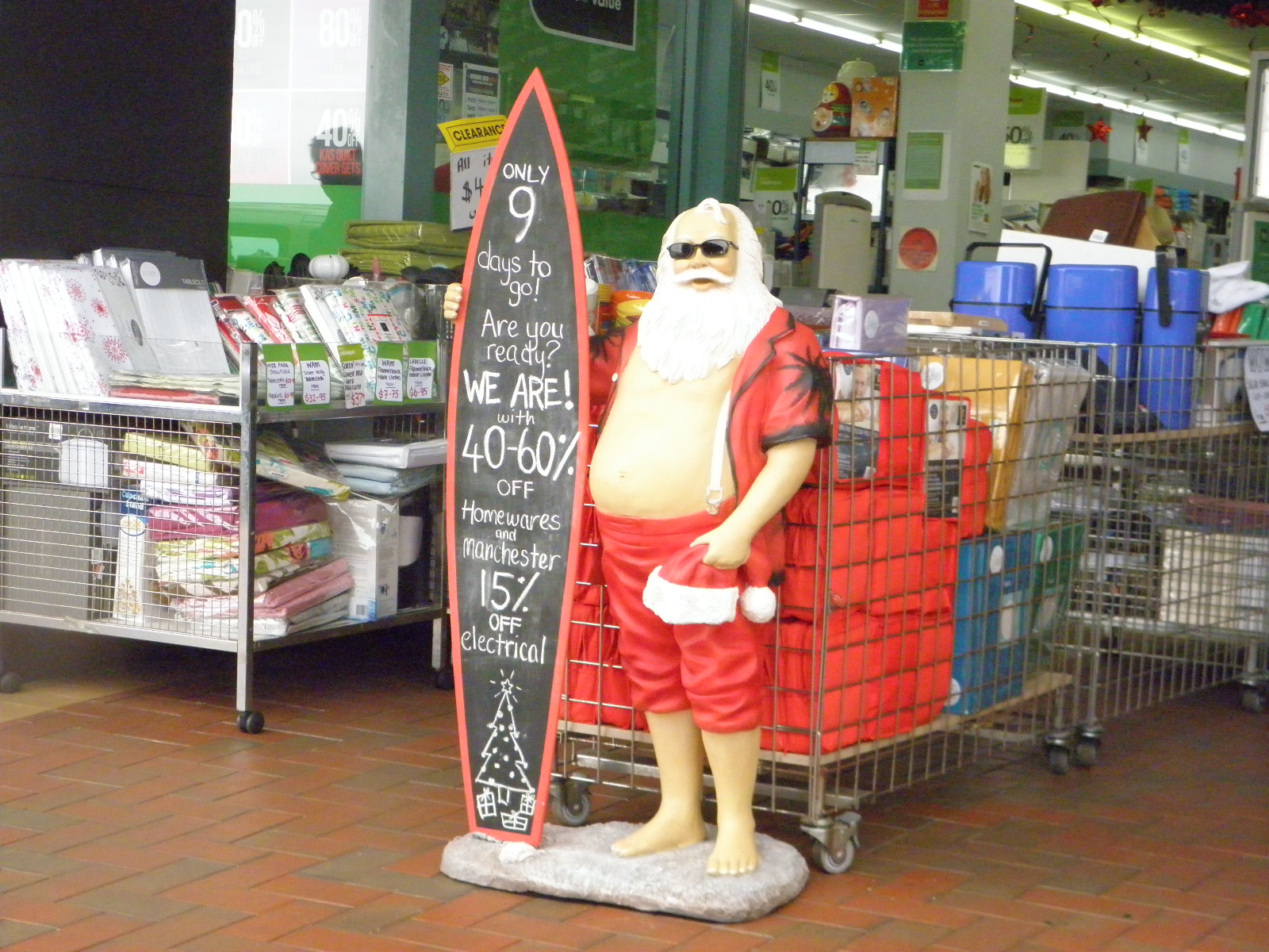 statue of santa with blackboard surfboard in front of homewares shop