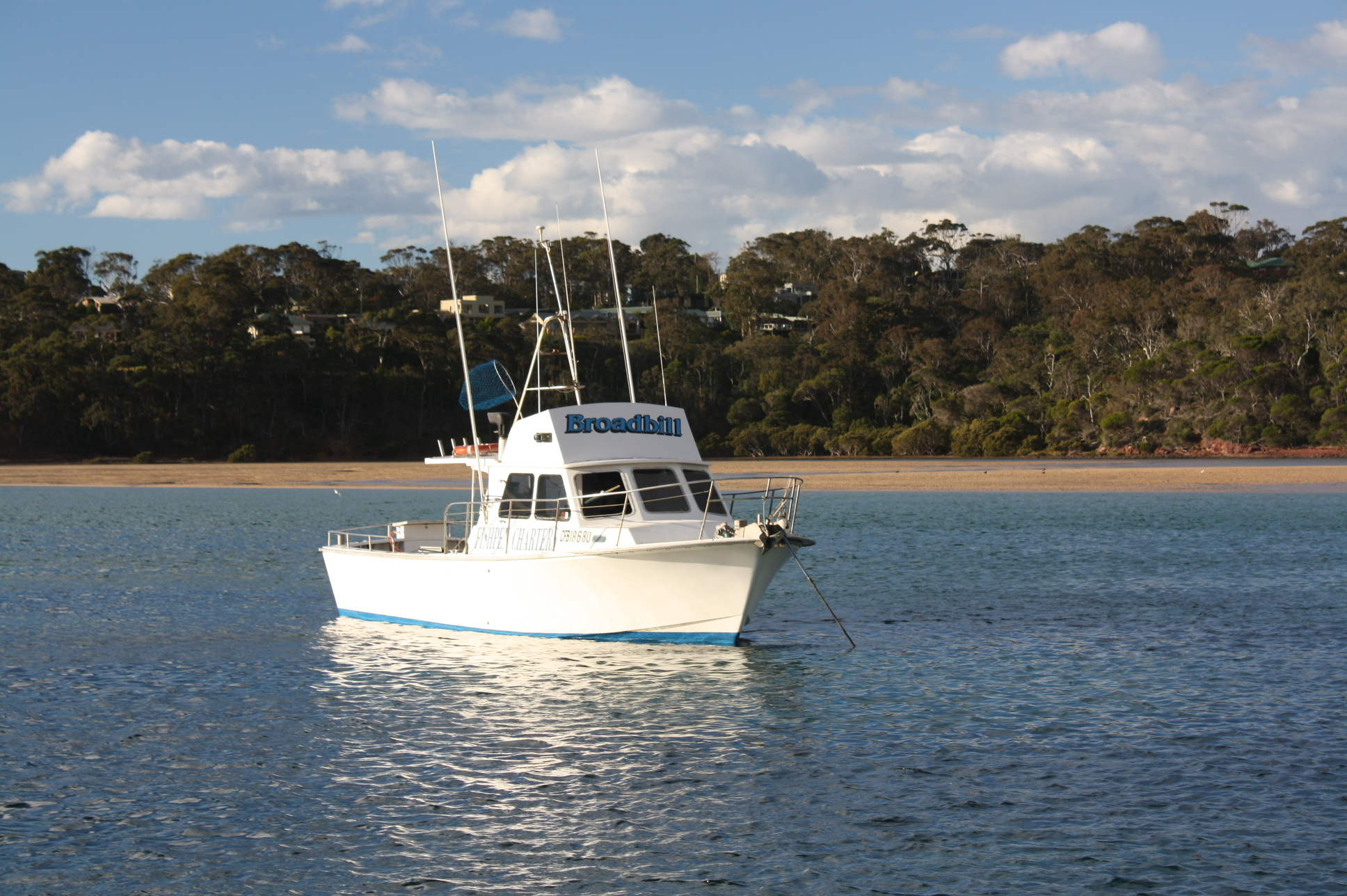 small white boat on merimbula lake at fishpen