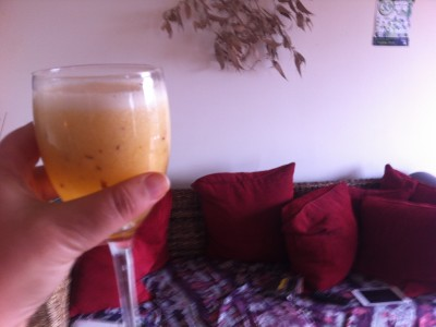 glass of wine fruit cocktail with red cushions in a couch