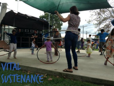 woman hoola hooping with children in background also hoola hooping