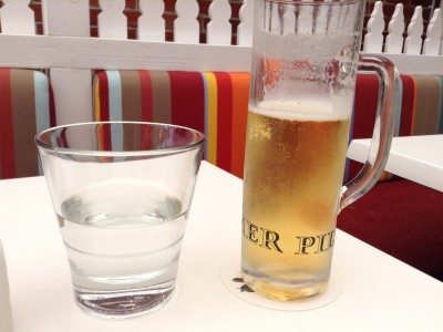 Glass of Pilsner beer and water in colourful courtyard cafe