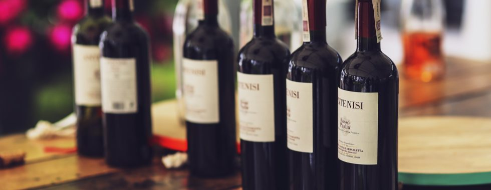 benefits of red wine - line of red wine bottles
