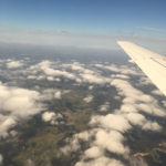 fluffy white clouds, plane wing and green earth below blue sky