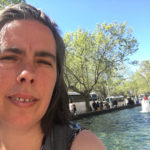 sarah looking at the camera in front of blue water and fountain at ngv