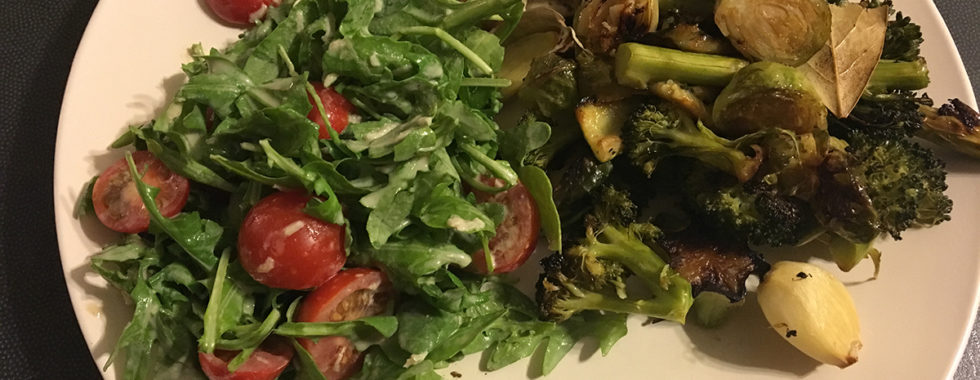 salad of tomatoes rocket and other green vegetables with chicken on side